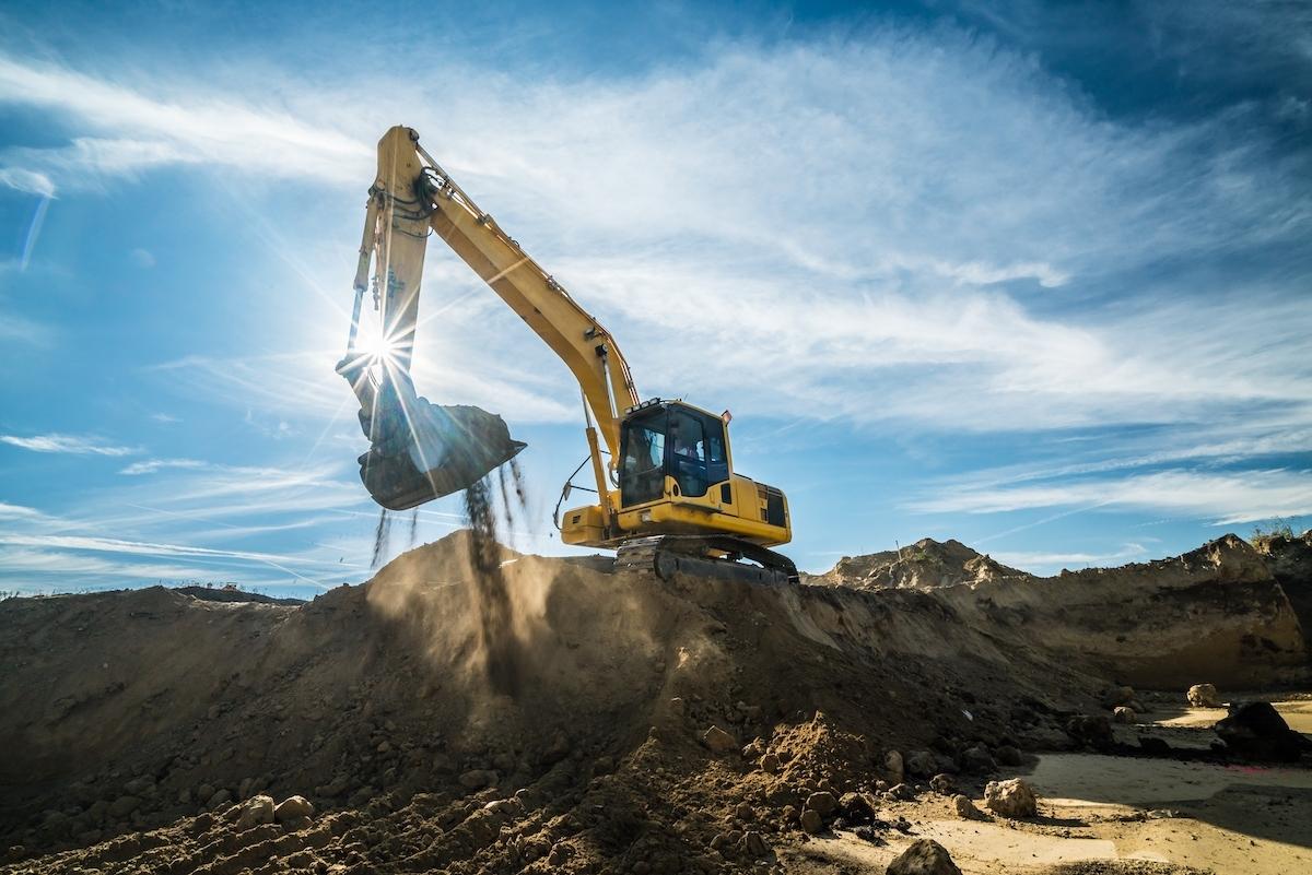 Grävskopa gräver i solsken.